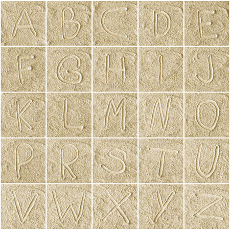 handwritten alphabet letters on sand background photo