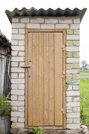 latrine: white brick outdoors toilet with wooden door, slate roof