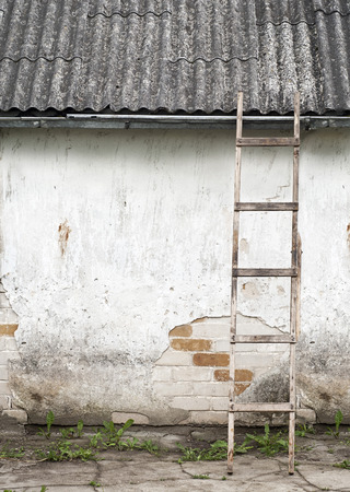 foundation cracks: old, weathered brick wall, ladder near the wall background