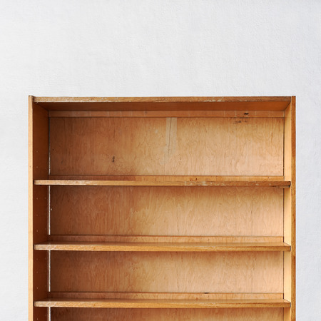 empty old retro wooden book shelf near the stucco wall
