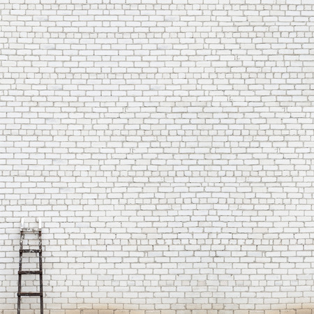 old brick wall: weathered white brick wall with wooden ladder background