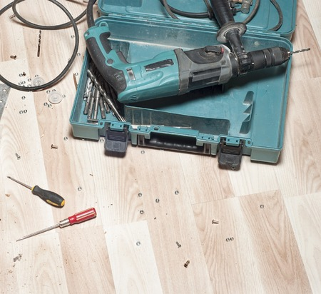 drill floor: Electric drill, bolts, screwdrivers  on wooden floor, wooden shavings, mess around after work