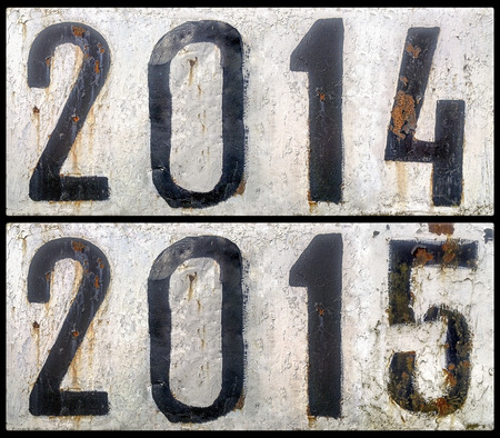 two rusty metal plates with a painted numbers 2014 and 2015. new year photo