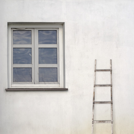 stucco wall with window and wooden ladder background photo