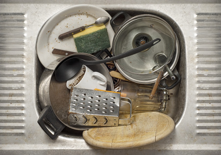 Dirty dishes, utensils in the metal sink background photo
