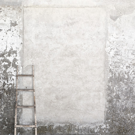 backstairs: weathered stucco wall with a wooden ladder background Stock Photo