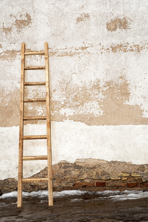crack climb: weathered stucco brick wall with wooden ladder background