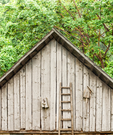 rungs: Old broken homemade bird houses under the roof of the shed