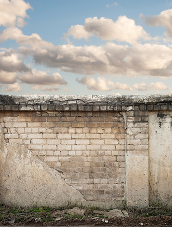 Blue sky with clouds behind the cracked wall background