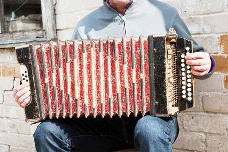 concertina: man playing with an old grunge concertina near the brick wall Stock Photo