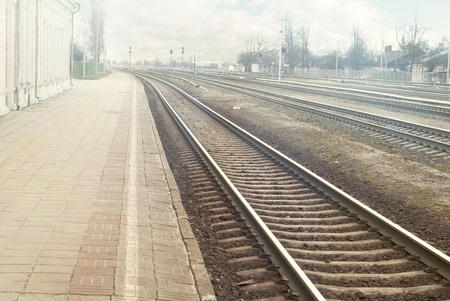 railroad station platform: Railroad station platform in a sunny day background, cloudy sky, sun flares Stock Photo