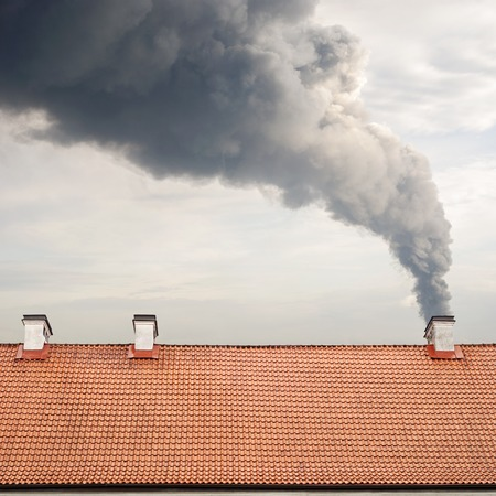 Huge dark smoke raising from a chimney, tiled brown roof