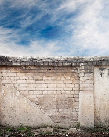 wall clouds: Blue sky with clouds behind the cracked wall background