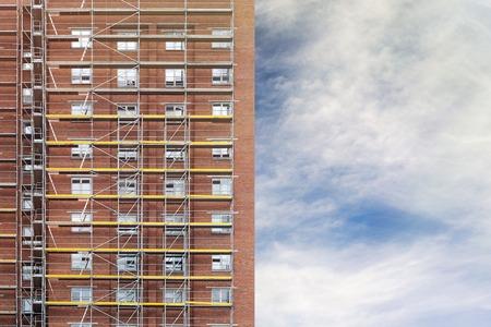 andamio: restauración de la fachada de la casa de altura, construcción de andamios, fondo del cielo nublado Foto de archivo