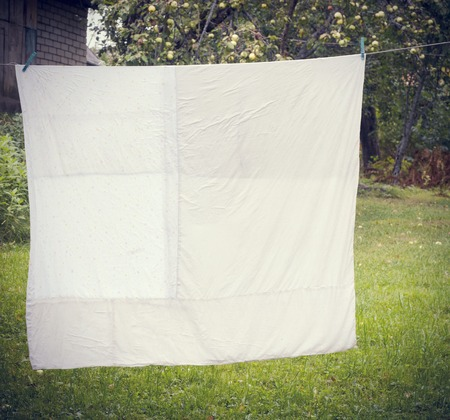 white washed duvet hanging in the yard