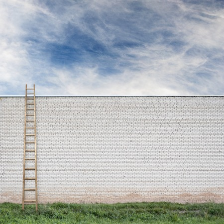 huge white brick wall with a wooden ladder, green grass and cloudy sky background