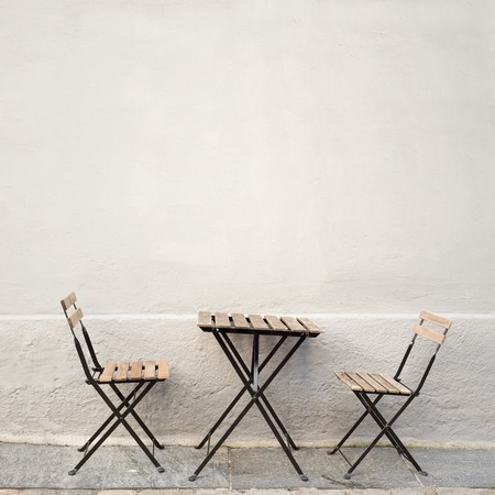 dining table and chairs: outdoor table and two chairs near the wall at coffee shop, Bergen, Norway Stock Photo