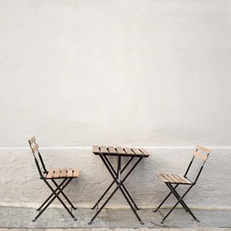 outdoor tafel en twee stoelen in de buurt van de muur bij coffee shop, Bergen, Noorwegen