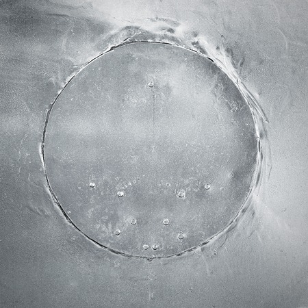 Round aged metal plate, scratched texture, abstract background