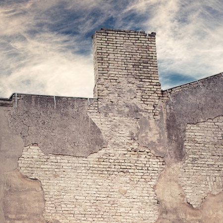 abandoned grunge cracked brick stucco wall of old house with chimney