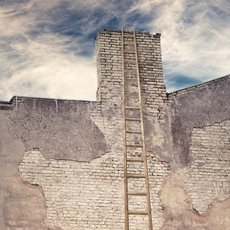 rungs: abandoned grunge cracked brick stucco wall of old house with chimney and ladder near the wall