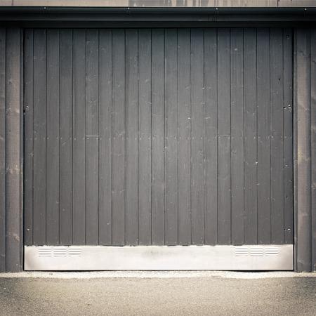 dark black wooden garage door, asphalt ground