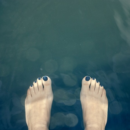 painted toes: Bare pedicure covered with blue feet  over the water Stock Photo