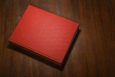 old book cover: Red book on the wooden scratched table