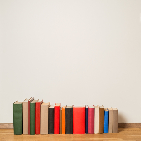 book racks: Old colorful books on wooden floor near the white wall