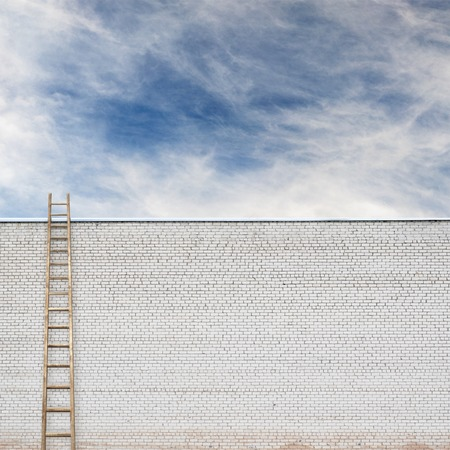 backstairs: huge white brick wall with a wooden ladder and cloudy sky background Stock Photo
