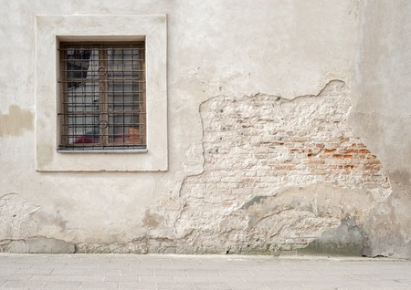 abandoned grunge cracked brick stucco wall with a window grilles Banco de Imagens - 57773092