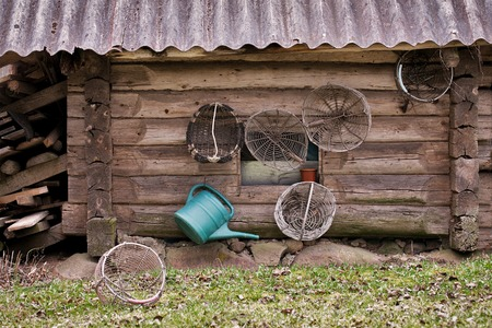 implements: Old grunge wooden house, garden baskets and watering can hanging on the wall