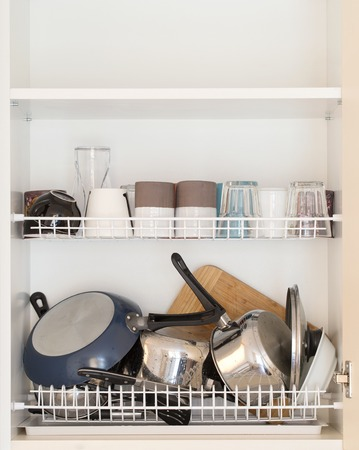 draining: lots of wet dishes in the dish draining closet Stock Photo