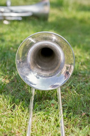part of silver trombone on th grass, close up image