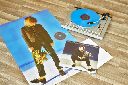 christine: VILNIUS, LITHUANIA - 2015: Christine and the Queens vinyl record Chaleur humaine album, record player with a vinyl on a wooden floor.