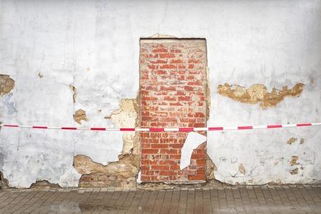cracked brick wall and bricked up door