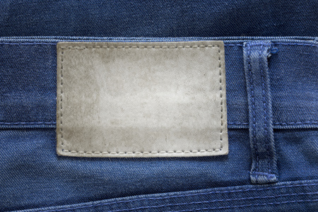 Blank grunge dirty leather label on a blue jeans Stock Photo