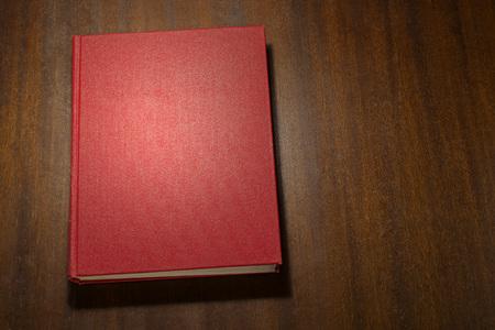 Rotes Buch auf dem Holz zerkratzt Tisch Standard-Bild - 78053134