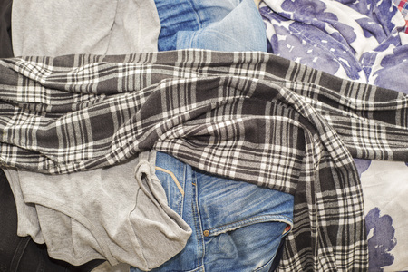 messy clothes: Lot of wrinkled clothes lying on sofa