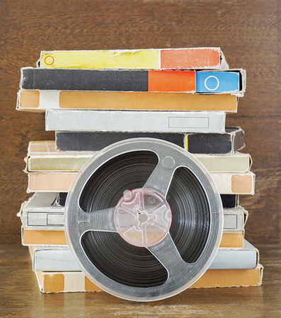 Vintage magnetic audio tapes, reel to reel type, paper box on the grunge wooden shelf Stock Photo