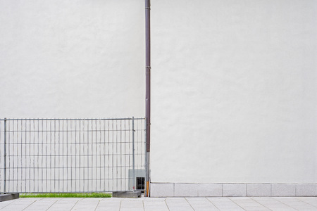 white wall with water pipe, metal security fence near the wall