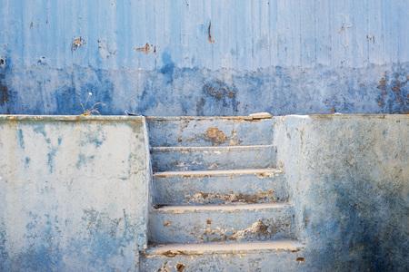 blue abandoned grunge cracked stucco wall and stairs Фото со стока