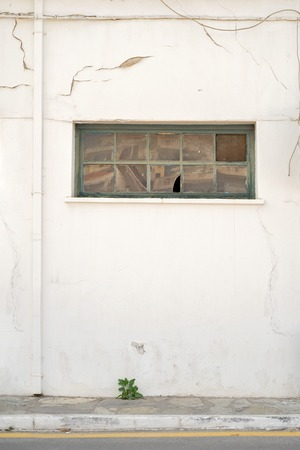 smudged: cracked white wall with window and rain water pipe