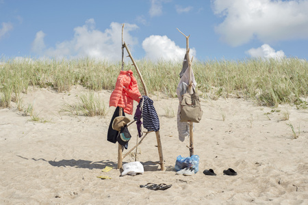 dry suit: clothes hanging on the wooden poles at the beach, windy, cold summer Stock Photo