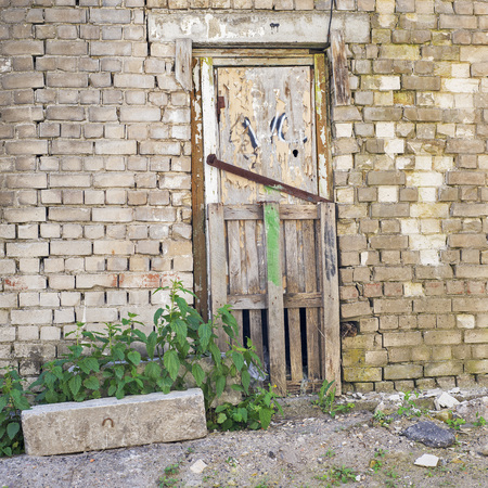 metal structure: grunge wooden door, cracked brick wall of an abandoned building