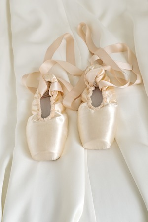 Ballet pointe shoes on beige color fabric background