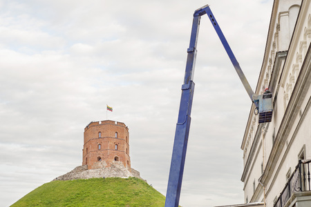 hydraulic lift: Gediminas tower on green hill with Lithuanian flag on top, construction worker fixing house facade using lifting boom machinery Stock Photo