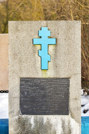 Old abandoned monument with blue cross at the cemetery of russian orthodox Stock Photo