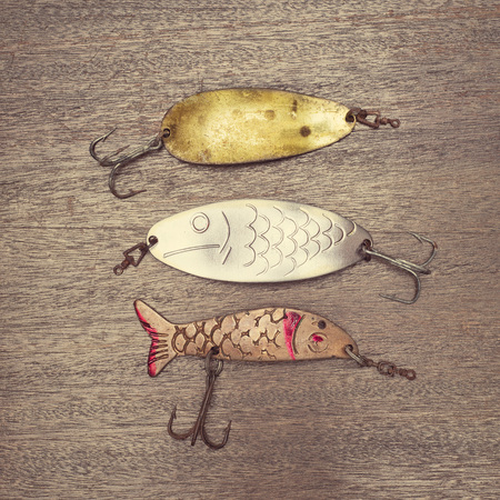 Three retro rusty lures on the wooden background