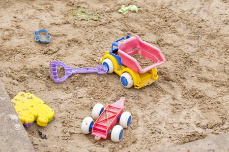 Children wooden sand box with some plastic toys Stock Photo
